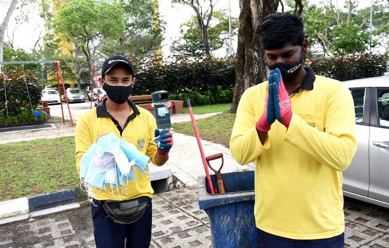 The Penang Island City Council workers pose with a handful of used facemasks collected. —  Photo courtesy of Facebook/Majlis Bandaraya Pulau Pinang