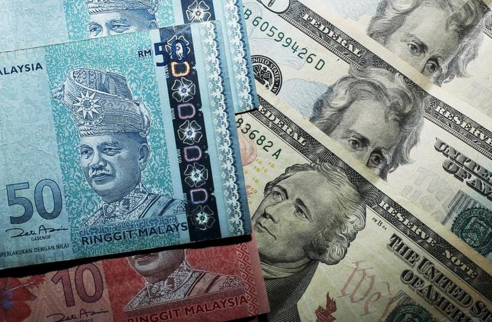 Malaysian ringgit notes are seen among US dollar bills in this photo illustration taken in Singapore in this August 24, 2015 file photo. — Reuters pic