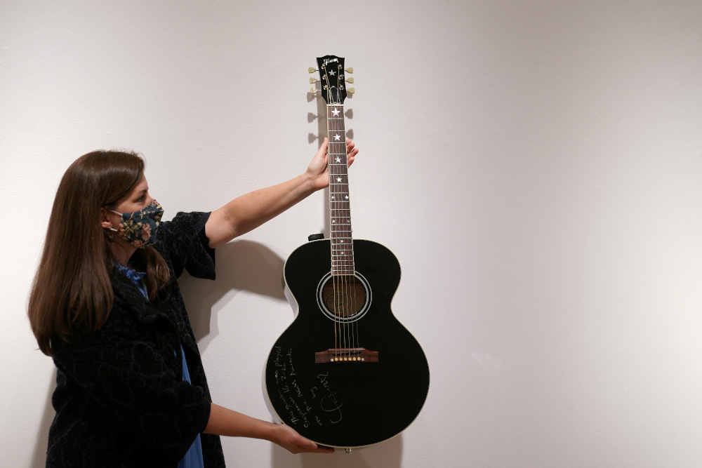 An employee of Christie's auction house holds a guitar used by singer Taylor Swift that will go up for sale as part of their Nashville Country auction in the Manhattan borough of New York October 14, 2020. — Reuters pic