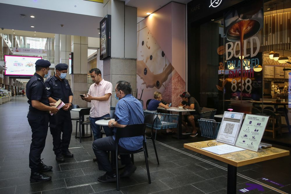 Police personnel check on mall-goers at Pavilion, Kuala Lumpur as the conditional movement control order kicked on October 14, 2020. — Picture by Yusof Mat Isa