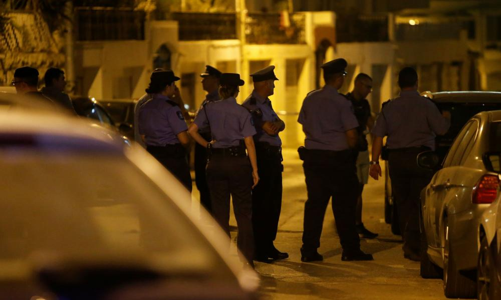 Police officers near the home of Melvin Theuma, after he was found unconscious in Swieqi.