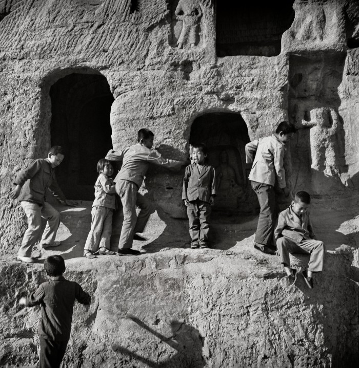 Boys play in the Yugang caves, one of China's earliest Buddhist sites