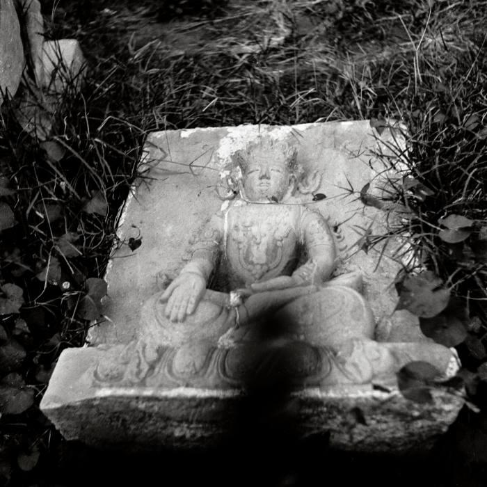 A marble Buddha lies discarded near the temple