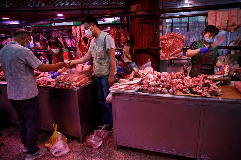 © Reuters. customer wearing a face mask pays for pork as a vendor chops pork meat inside the Yuegezhuang wholesale market, following new cases of coronavirus disease (COVID-19) infections in Beijing