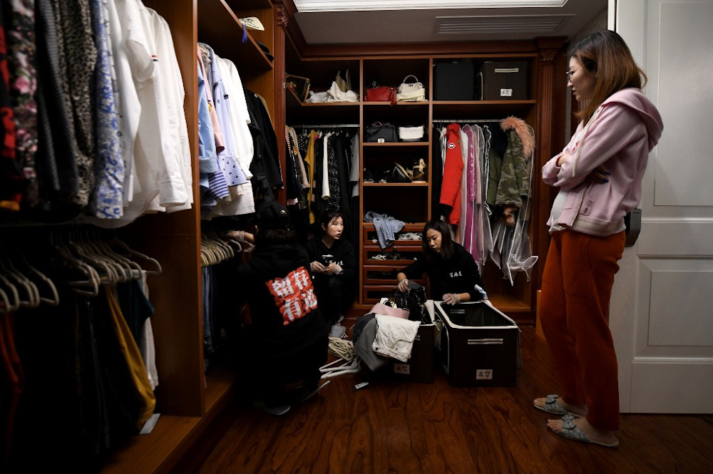 This photo taken on October 26, 2020, shows home organisers arranging the luxury wardrobe of client Chen Rui (right) in Beijing. — AFP pic