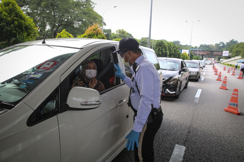 A traffic policeman conducts checks on vehicles during a roadblock on Jalan Sultan Ismail in Kuala Lumpur October 14, 2020. — Picture by Yusof Mat Isa