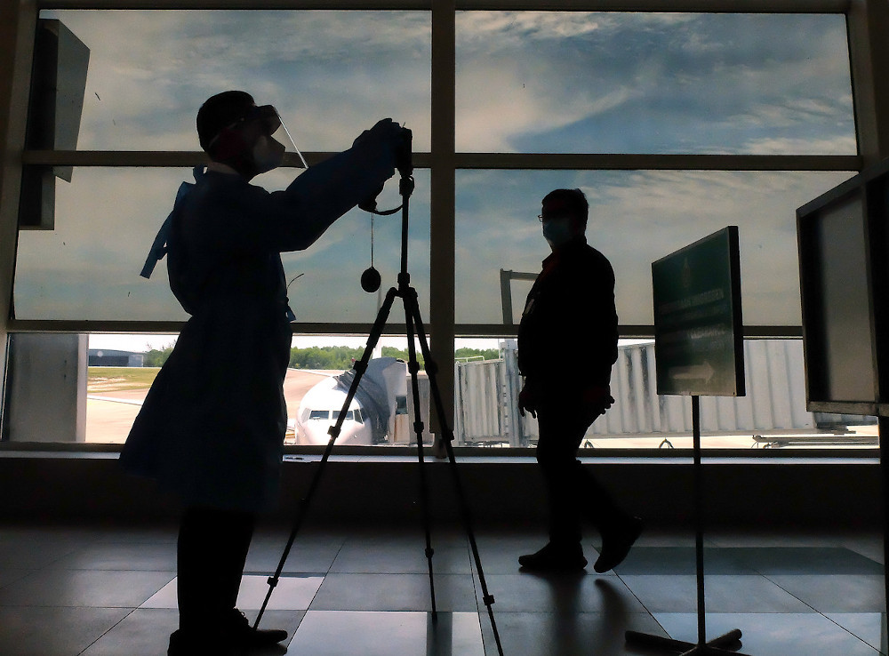 A Health Department Personnel setting up the Forward-Looking Infrared (FLIR) High Definition Thermal Camera for temperature screening at the arrival hall in Labuan Airport August 10, 2020. — Bernama pic