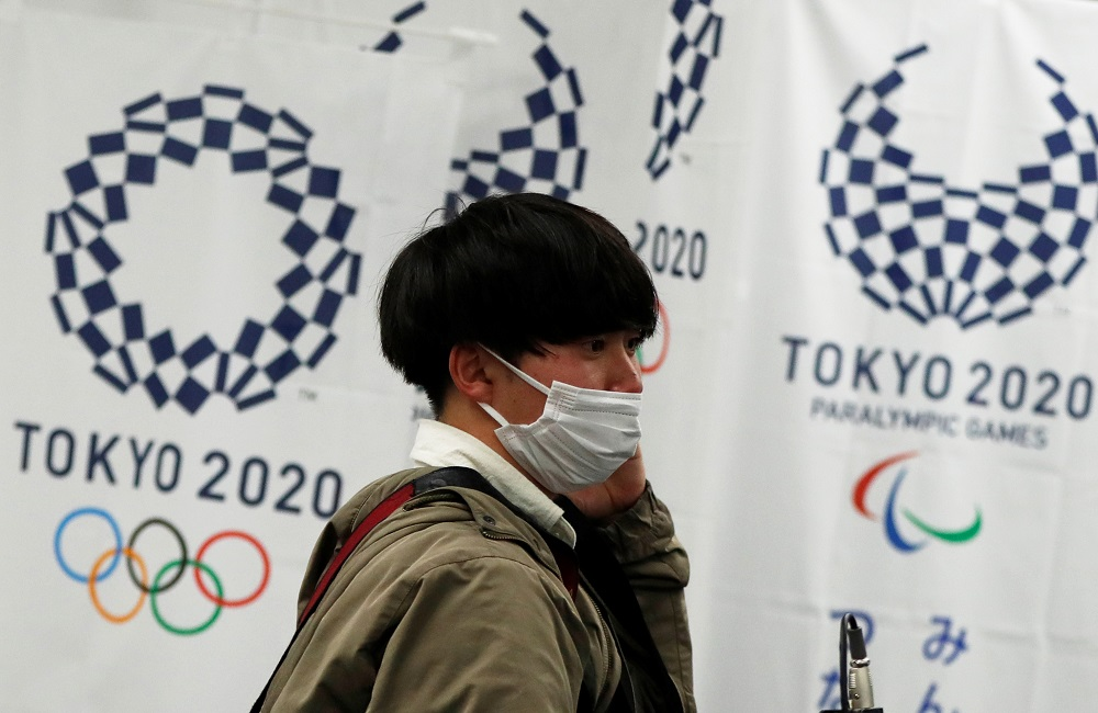 A man wearing a protective face mask walks in front of flags of the Tokyo 2020 Olympic and Paralympic Games in Tokyo March 17, 2020. — Reuters pic
