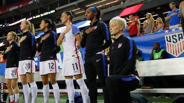 Megan Rapinoe kneels for the US national anthem