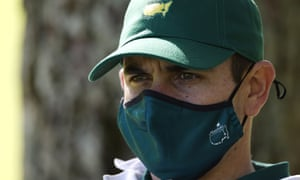 A caddie wearing a Masters mask stays vigilant during a practice round for this week's tournament.
