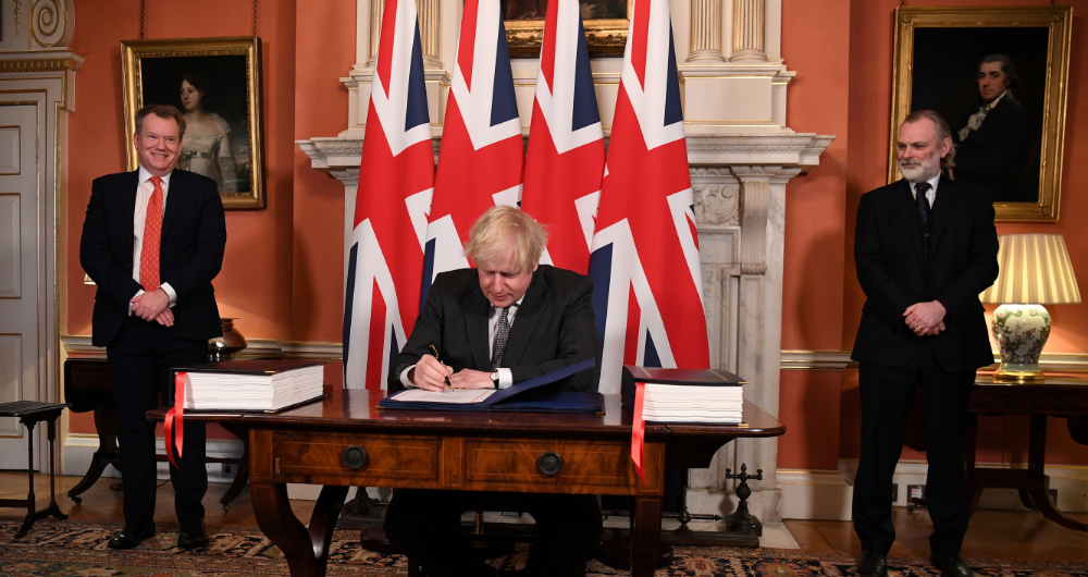 Image Caption : UK chief trade negotiator David Frost and British Ambassador to the EU Tim Barrow look on as Britain's Prime Minister Boris Johnson signs the Brexit trade deal with the EU at number 10 Downing Street in London, Britain December 30, 2020. (Reuters)