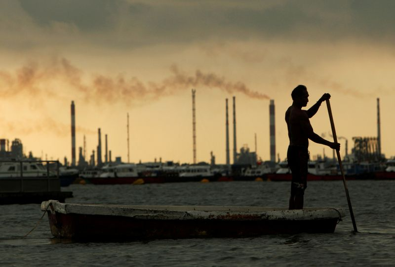 © Reuters. FILE PHOTO: A fisherman rows his dinghy past oil refineries near port terminals in Singapore