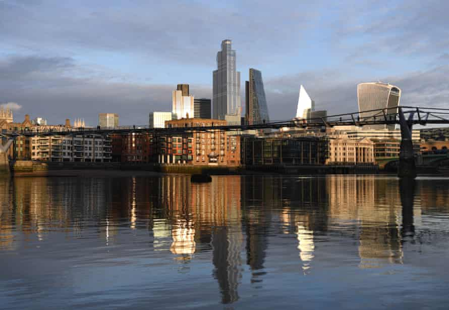 The City of London skyline is reflected in the River Thames, as Covid curbs continue to batter Britain's economy.