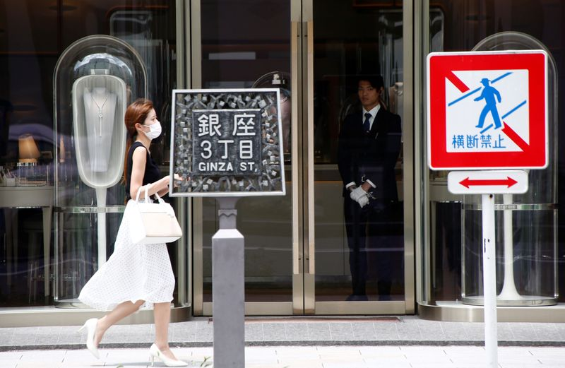 © Reuters. A woman walks past a luxury brand shop at a shopping district in Tokyo