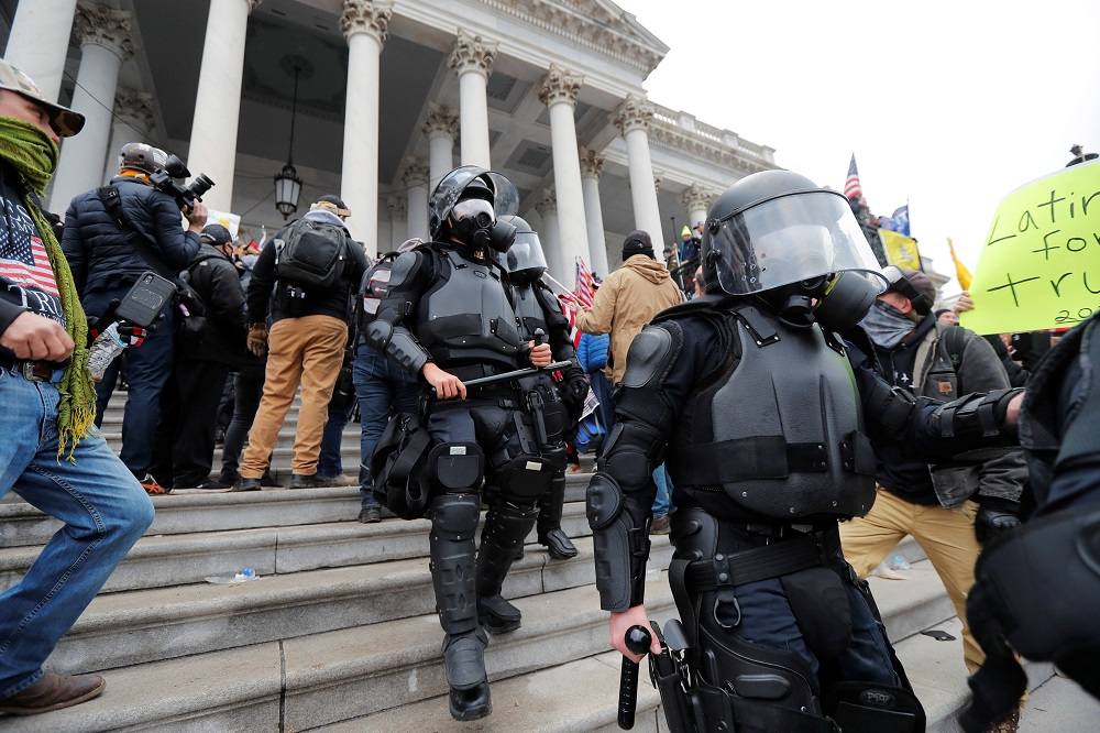 Law enforcement officers walk down the steps of US Capitol during a protest against the certification of the 2020 US presidential election results by the US Congress, in Washington January 6, 2021. — Reuters pic