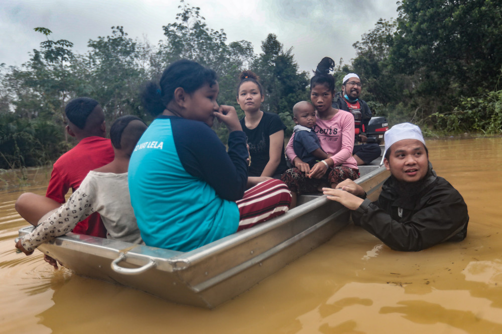 Preacher Ustaz Ebit Lew (in water) sent food to an Orang Asli village in Pekan, Pahang whose supply had been cut off due to flood. — Picture via Facebook/ Ebit Lew
