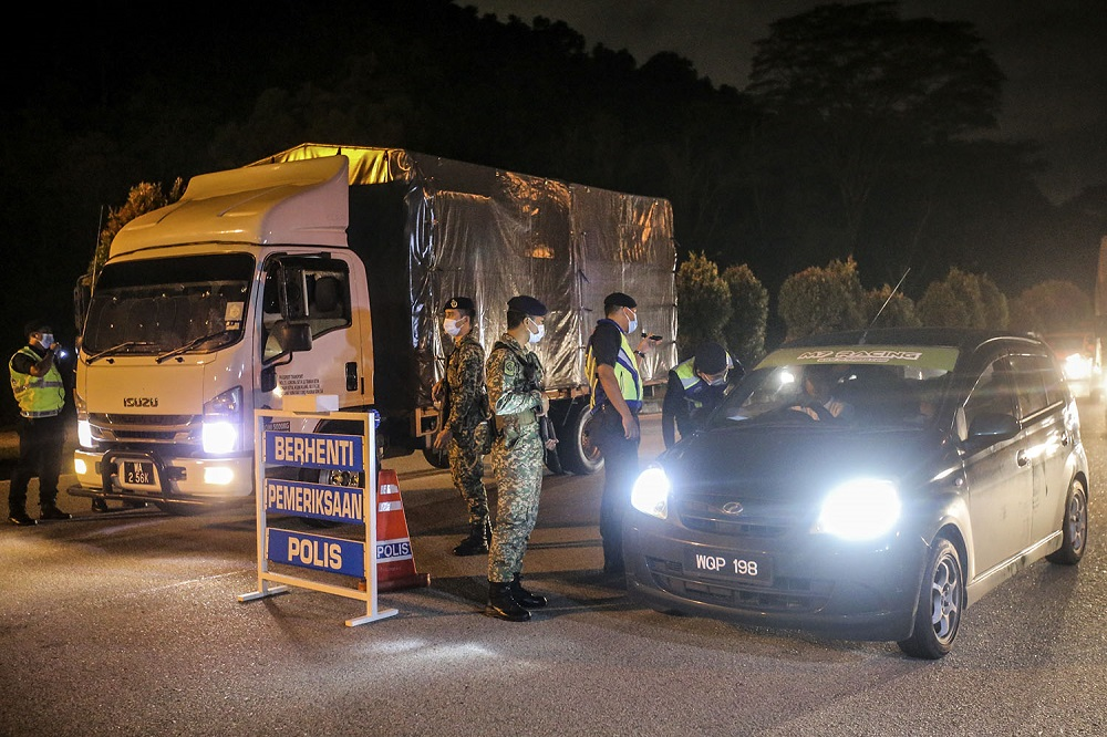Police officers man a roadblock at the Gombak Toll Plaza, January 12, 2021. ― Picture by Hari Anggara