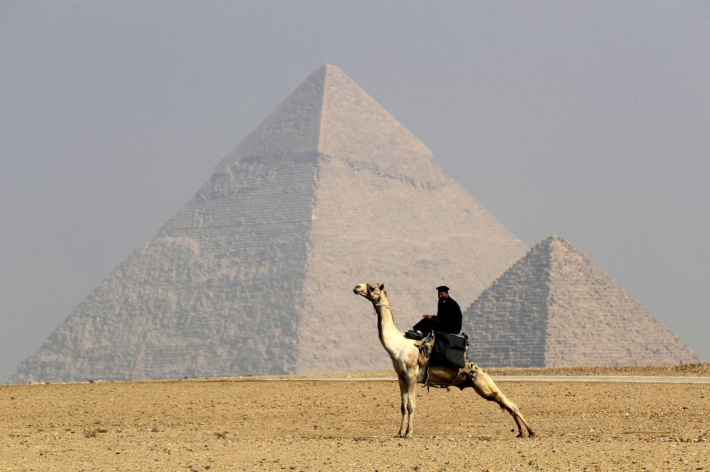 A mask-clad Egyptian policeman rides a camel in front of the Giza Pyramids on the southwestern outskirts of the Egyptian capital Cairo, on December 18, 2020. (File/AFP)