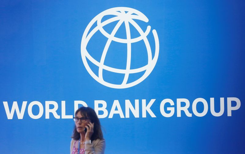 © Reuters. A participant stands near a logo of World Bank at the International Monetary Fund - World Bank Annual Meeting 2018 in Nusa Dua