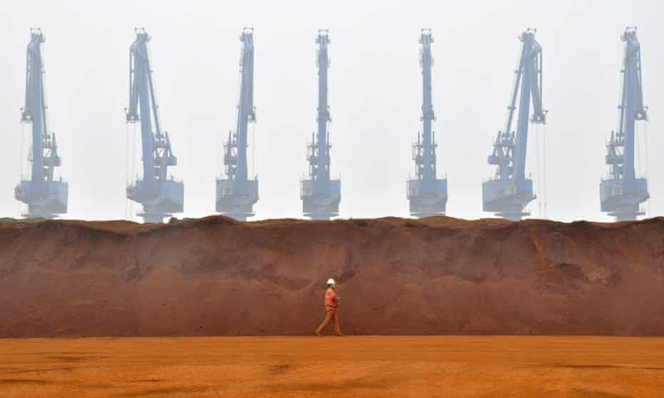 A worker walks past huge piles of red-orange iron ore