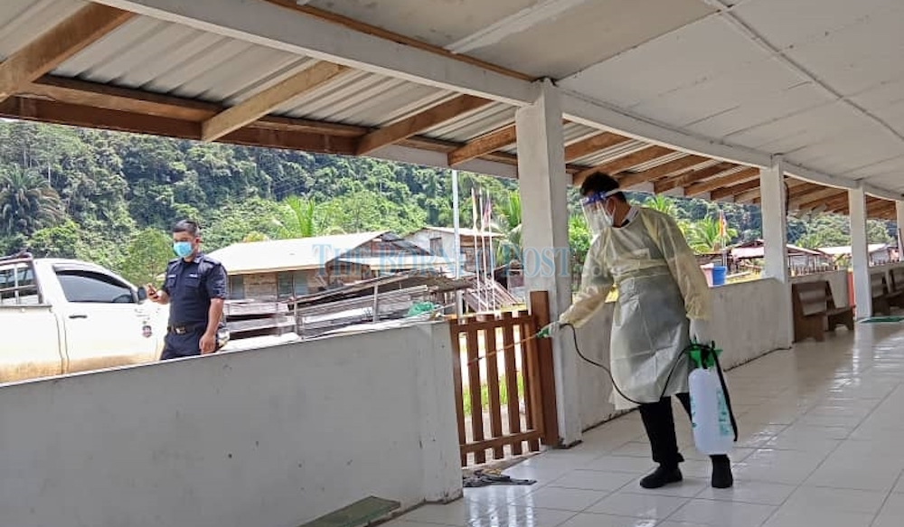 Medical personnel sanitising a section of a longhouse during the height of the Covid-19 pandemic in Sarawak in this file photo. — Photo courtesy of Borneo Post