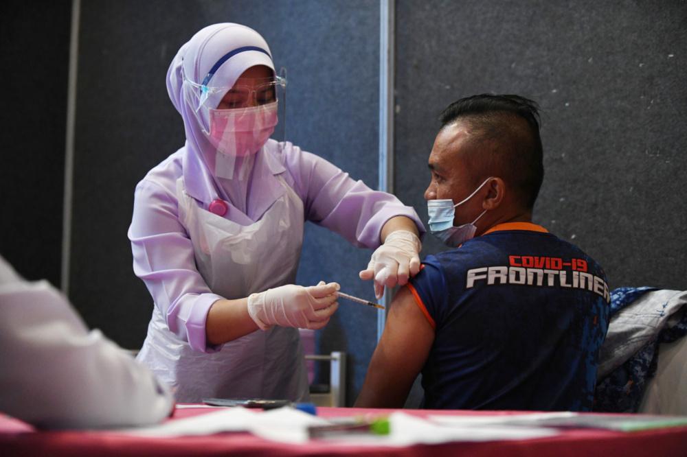 A frontliner receives the Pfizer BioNTech Covid-19 vaccine at the Kuantan Vaccination Centre at Dewan Jubli Perak Sultan Ahmad Shah in Kuantan, February 26, 2021. — Bernama pic