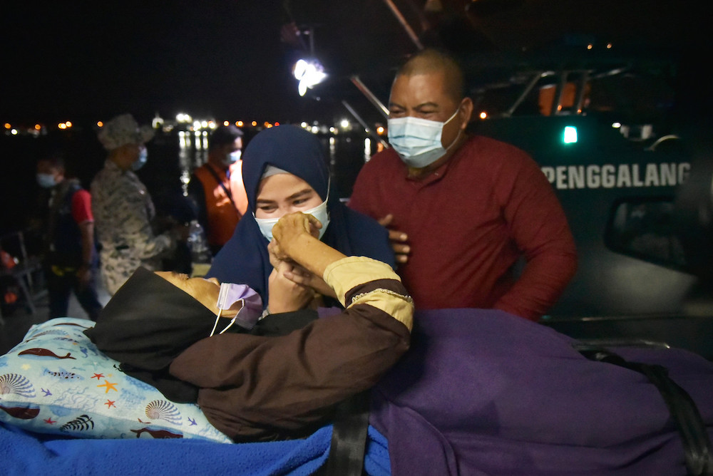 Salmah Adeh (left) finally meeting with her nephew Zamain Ma'in (right) and family at the Labuan International Ferry Terminal jetty, February 27, 2021. — Bernama pic