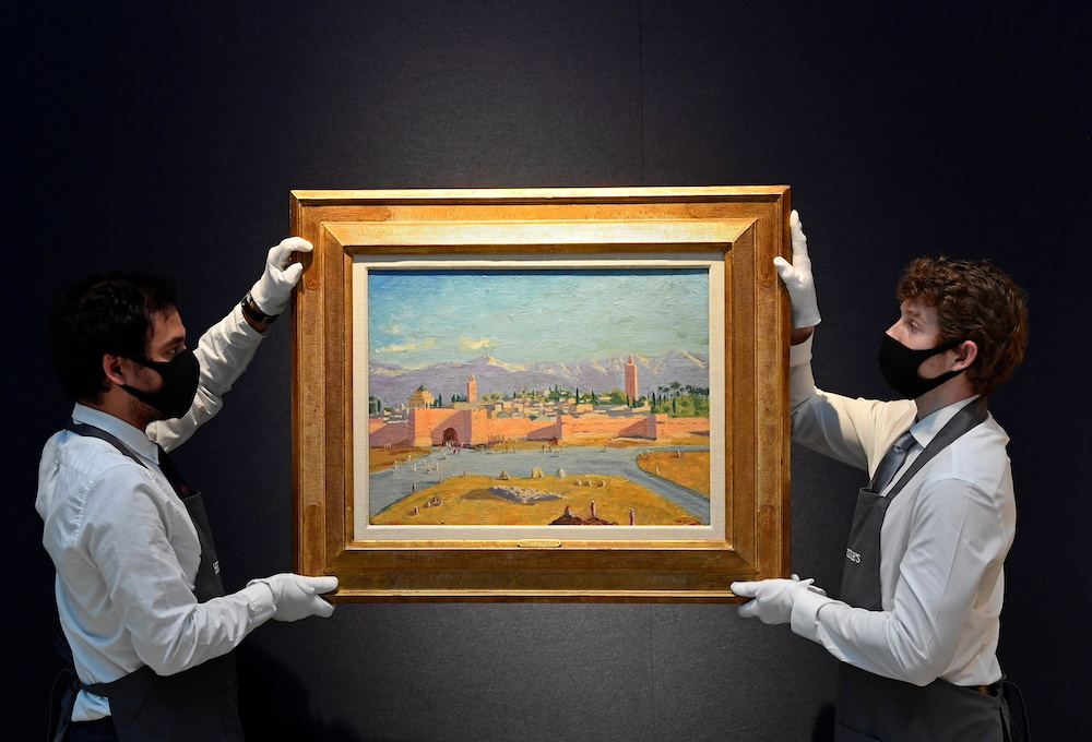 Art handlers pose with 'Tower of the Katoubia Mosque' painted by former British Prime Minister Winston Churchill in 1943, as preparations take place at Christie's ahead of a livestream auction of Modern British Art on March 1, in London. — Reuters pic