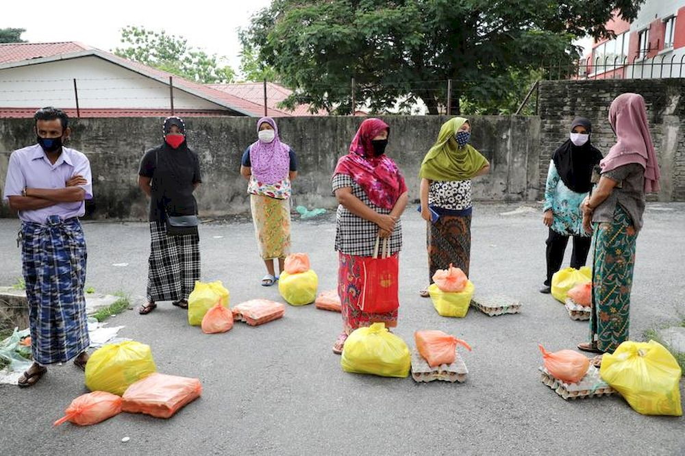 File picture shows Rohingya refugees wearing protective masks keep a social distance while waiting to receive goods from volunteers, during the movement control order due to the outbreak of the coronavirus, in Kuala Lumpur, April 7, 2020. — Reuters pic