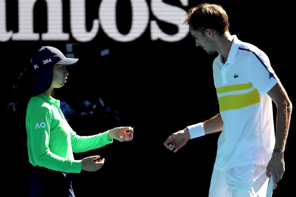 A ballkid hands over a feather to Russia's Daniil Medvedev who was looking for his missing racquet dampener during men's singles quarter-final match against Russia's Andrey Rublev at the Australian Open in Melbourne, February 17, 2021. — AFP pic