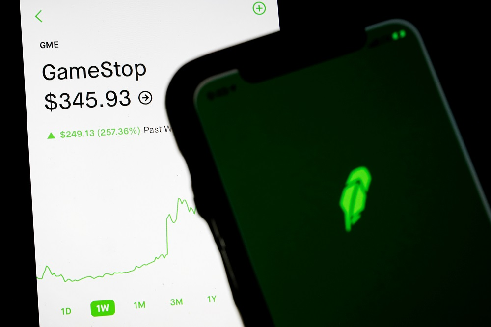 Trading information for GameStop is displayed on the Robinhood App as another screen displays the Robinhood logo in this photo illustration January 29, 2021.  — Reuters pic