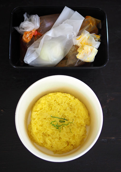 The 'pulut kuning' is packed in a container that makes it easy to eat on the go with the 'rendang' on the side.