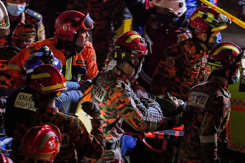 Fire and Rescue Department personnel carry a victim out of the collapsed part of the flyover that was still under construction in Kuala Lumpur, March 3, 2021. — Bernama pic