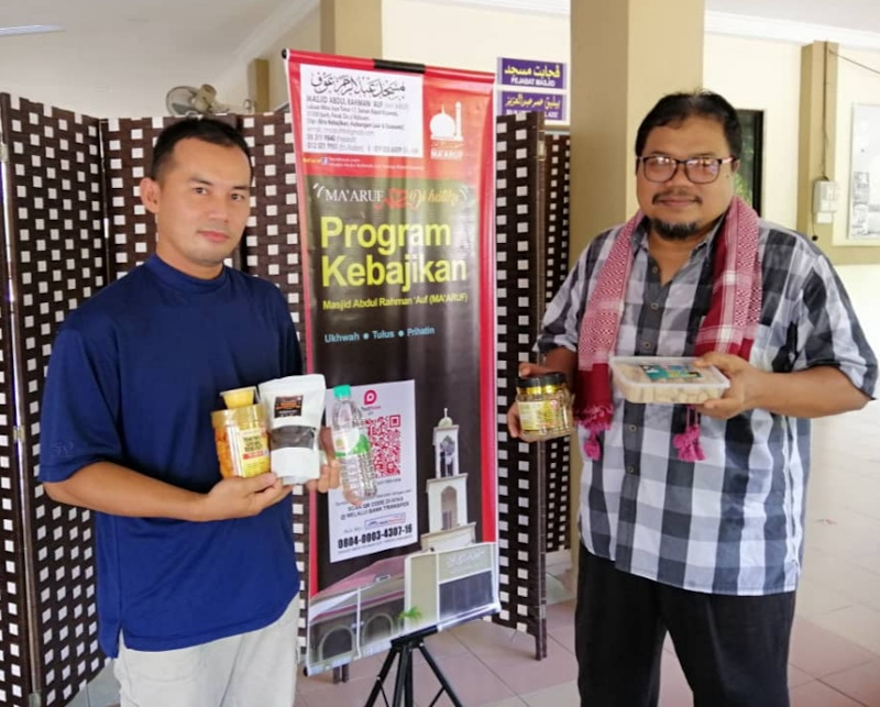 Masjid Abdul Rahman 'Auf's committee member Muhamad Akhyar Asnawi (right) and assistant secretary Mohd Yazid Soib with the food items sold at the mosque on Fridays as part of their fund raising activity. — Picture by Sylvia Looi