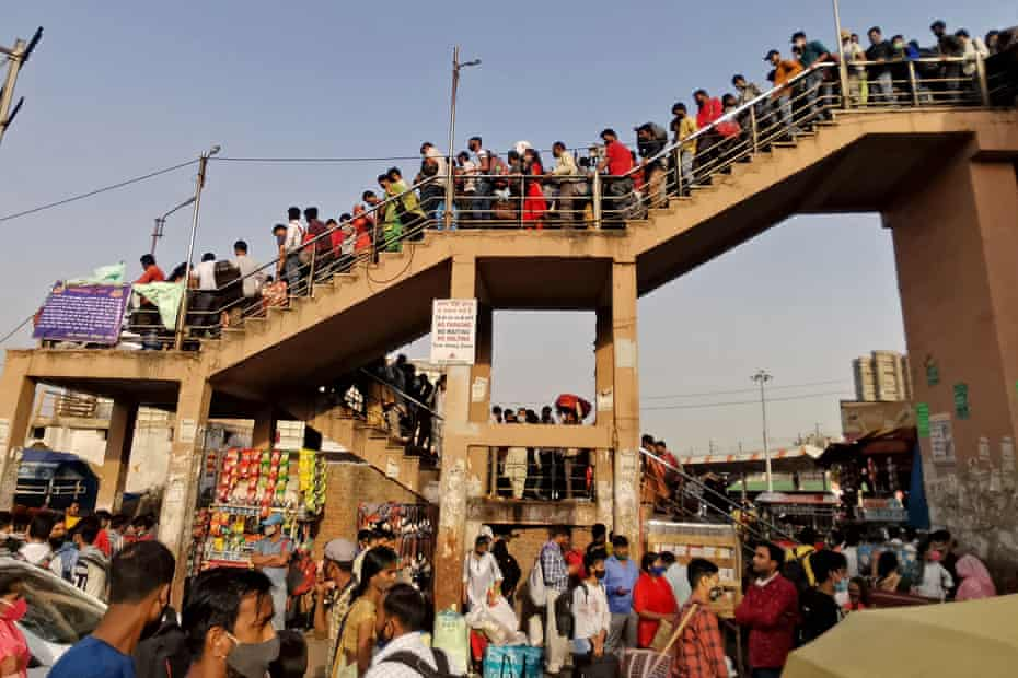 People crowd at a bus station on 19 April, hours before a week-long lockdown ordered by the Delhi government comes to effect