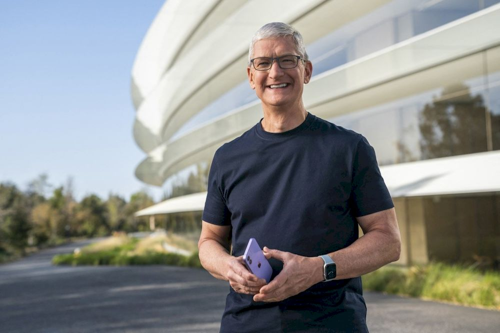 This handout released and taken on April 20, 2021 by Apple inc. shows Apple CEO Tim Cook holding a new purple iPhone 12 during a special event at Apple Park in Cupertino, California. — AFP pic