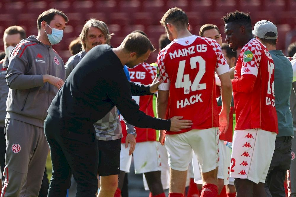 Mainz' Danish head coach Bo Svensson celebrates with his players including Mainz' defender Alexander Hack (centre) after the Bundesliga match Mainz 05 vs FC Bayern Munich, in Mainz, Germany, April 24, 2021. — AFP pic