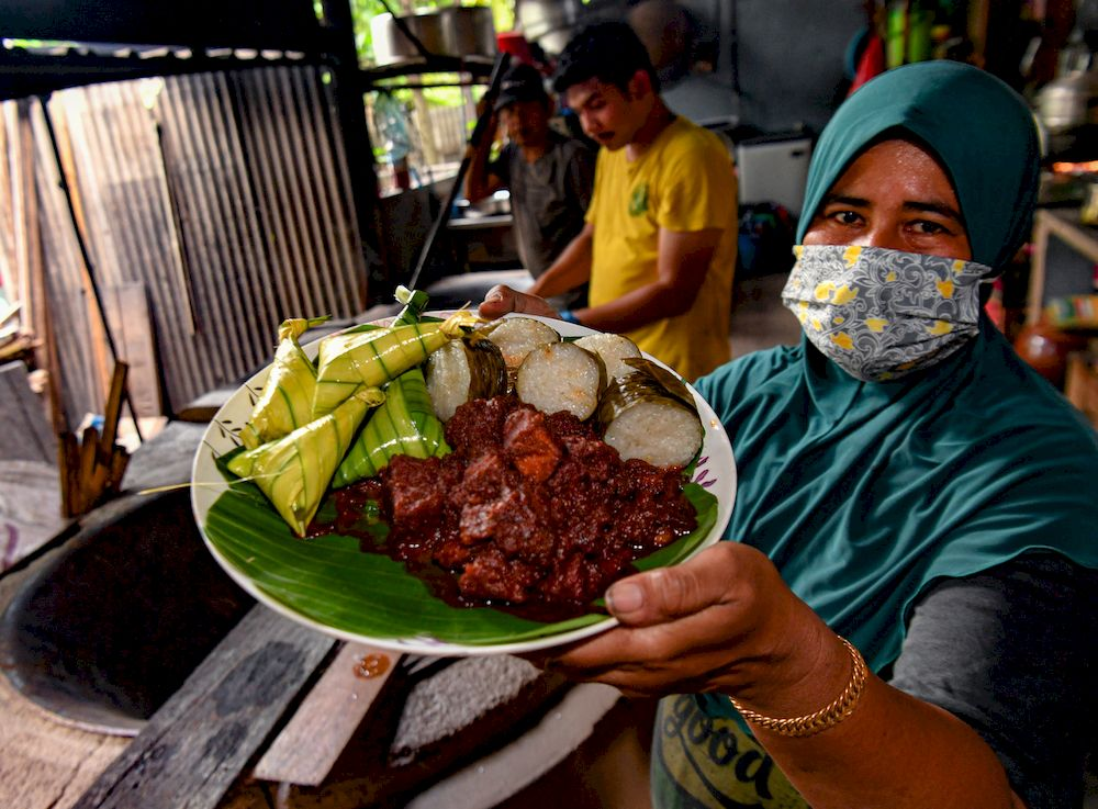 Huda Mat Isa (right) shows a rendang tok dish in Kampung Pasir Putih, Ipoh, April 24, 2021. — Bernama pic