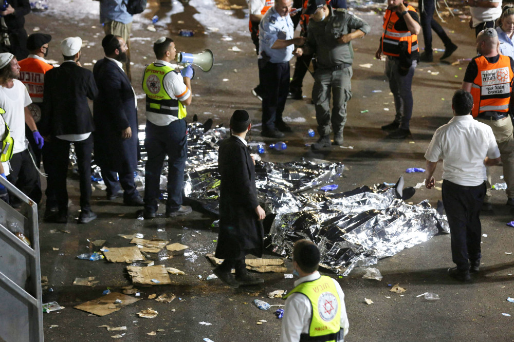 Videos posted on social media showed chaotic scenes as Ultra-Orthodox men clambered through gaps in sheets of torn corrugated iron to escape the crush