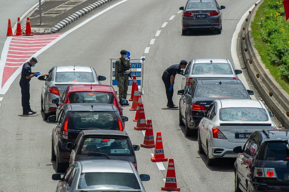 Police officers conducting checks at a roadblock in Jalan Kuching, Kuala Lumpur January 31, 2021. — Picture by Shafwan Zaidon