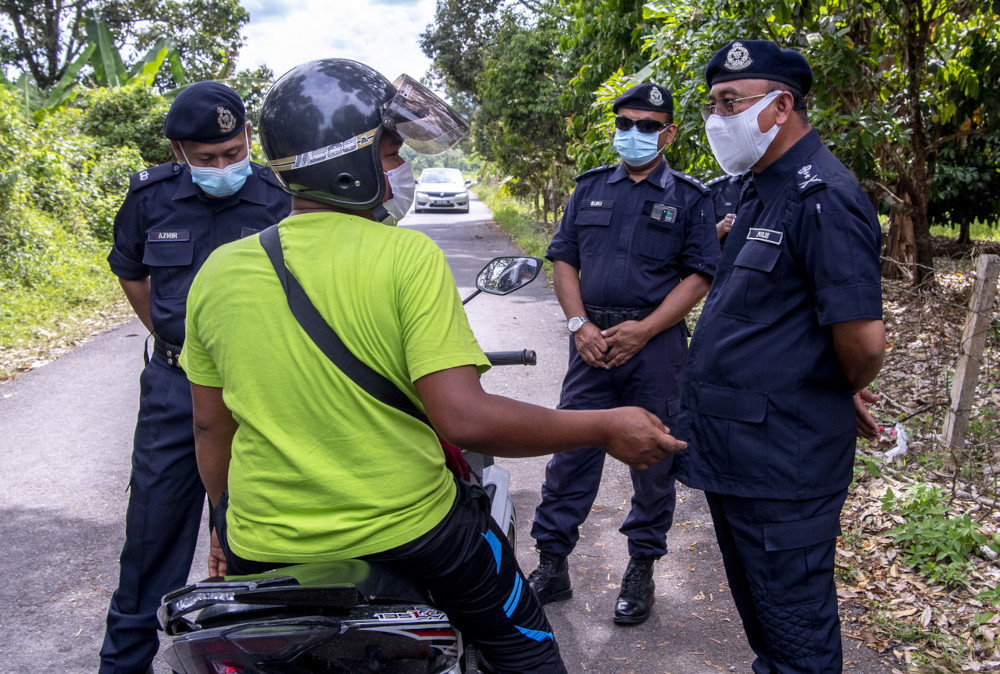 Kelantan police chief Datuk Shafien Mamat quizzes a motorist using a rat trail to neighbouring Terengganu at Jalan Kampung Gong Jenarah Bukit Yong, April 23, 2021. — Bernama pic