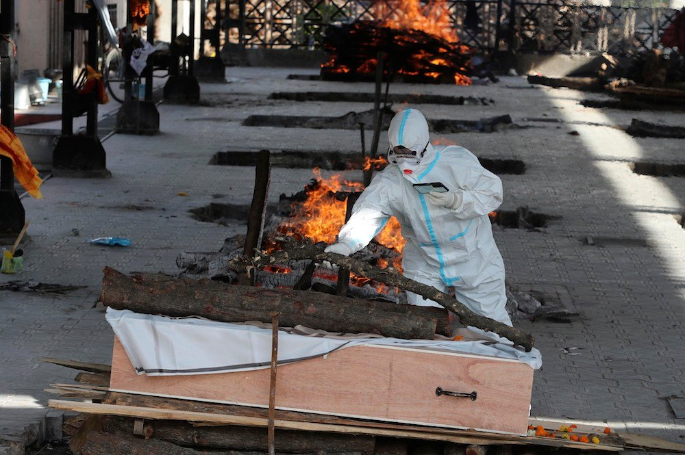 A man performs the final rites of a relative who died of COVID-19, at a crematorium in Jammu, India, Friday, April 23, 2021. (AP)