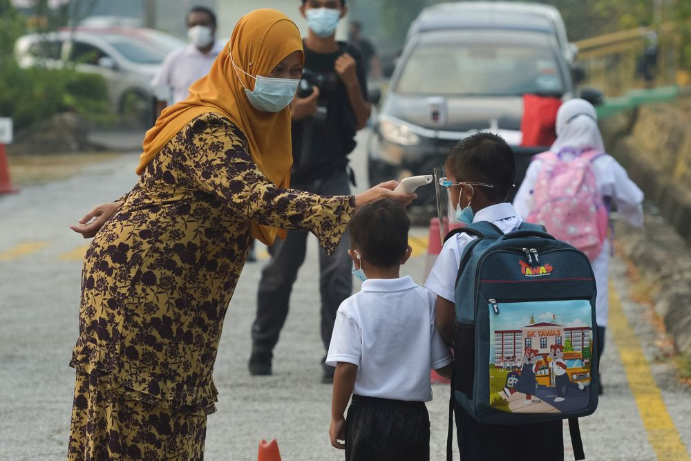 Sekolah Kebangsaan Seksyen 16 students have their temperature checked on their first day back at school in Shah Alam March 1, 2021. — Picture by Miera Zulyana