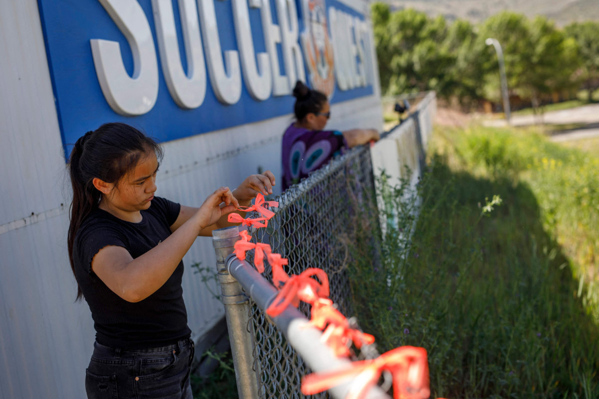 Young girls place ribbons on the fence behind the former Kamloops Indian Residential School in honor of the 215 children whose remains were found buried. (AFP / Cole Burston)