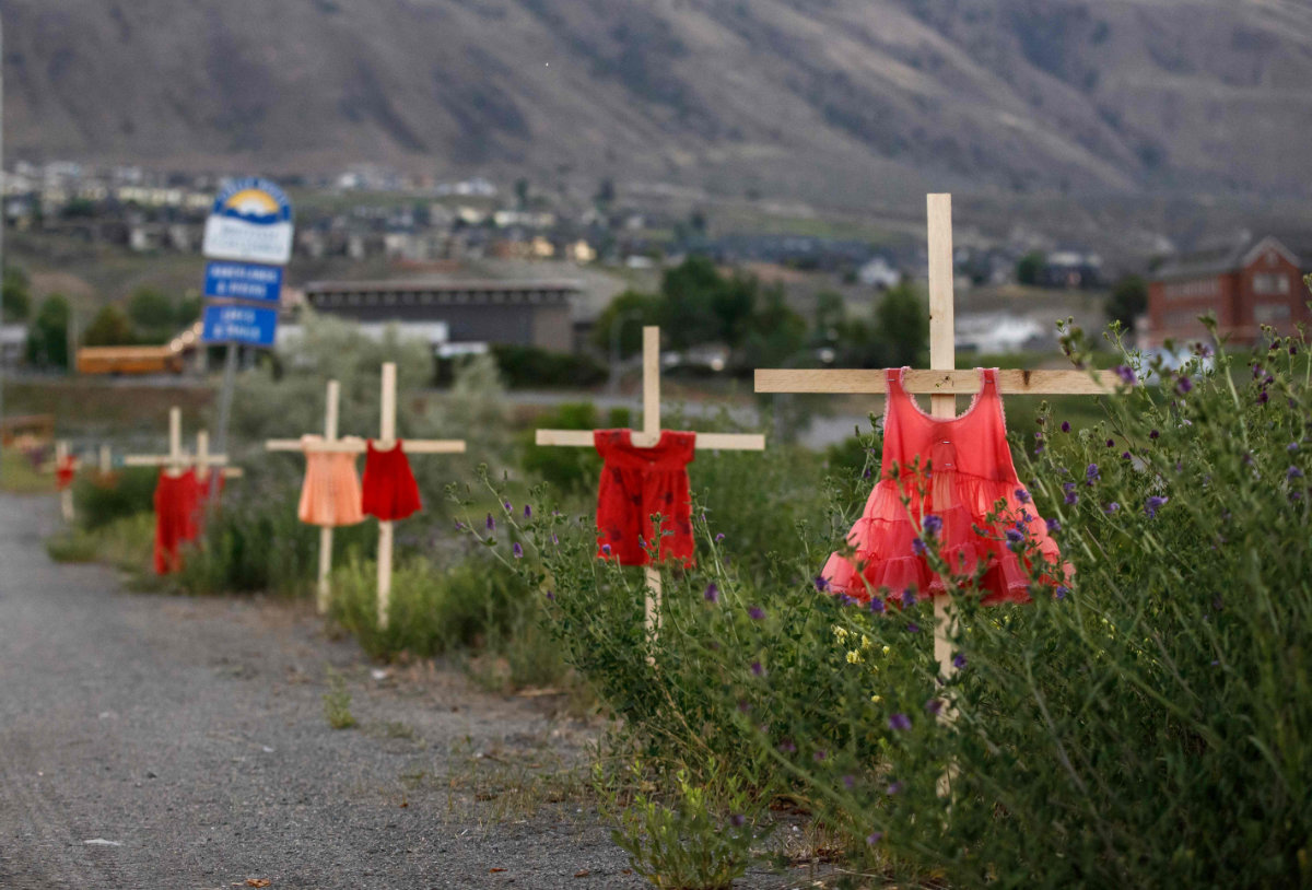 Children's red dresses are staked along a highway in Kamloops, British Columbia, Canada, where the remains of 215 school children have been discovered buried. (AFP / Cole Burston)