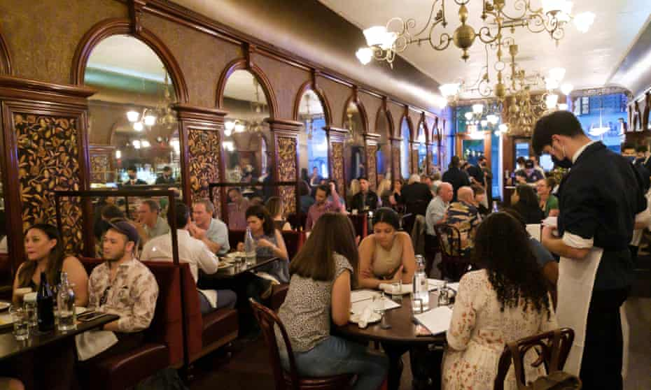 People sit at tables in a nearly full restaurant in the Brooklyn borough of New York.