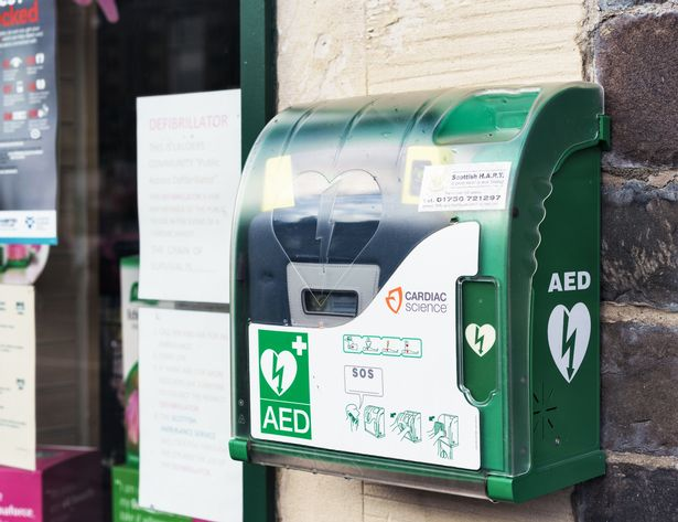 An automated external defibrillator sits a building wall on a street, giving 24-hour 24 availability in case of an emergency