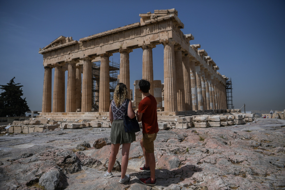 A couple visit the Parthenon temple on the archeological site of the Acropolis in Athens May 18, 2020 amid the pandemic of the novel coronavirus. — AFP pic
