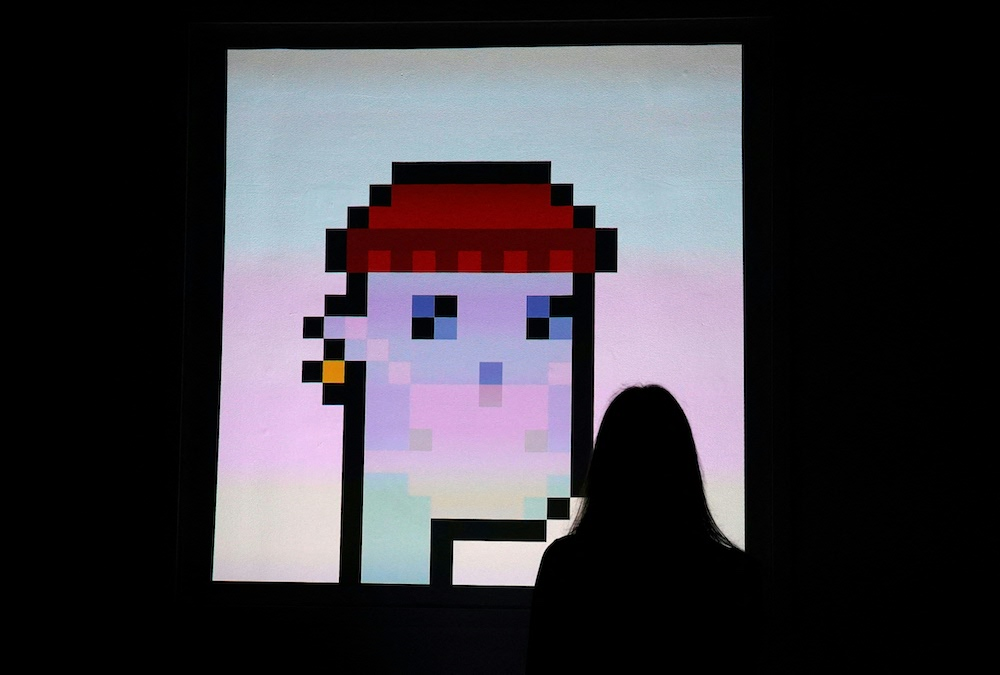 A woman looks at an NFT by Larva Labs titled 'CryptoPunk 7523' during a media preview on June 4, 2021, at Sotheby's. — AFP pic