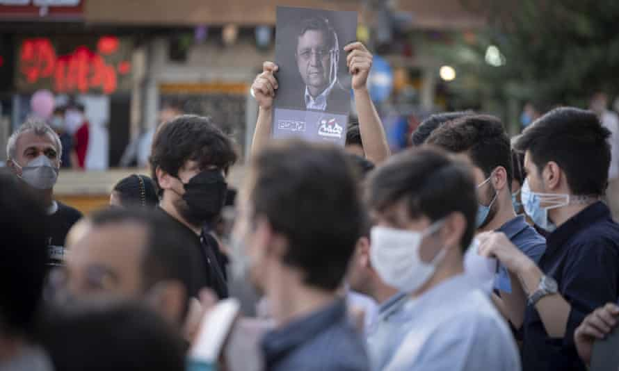 A supporter of the presidential election candidate Abdolnaser Hemmati holds up a poster at an election campaign in Tehran.